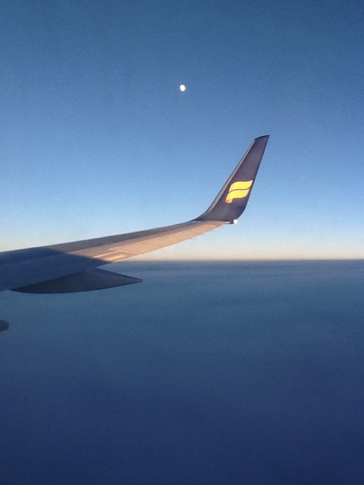 Taken at mid-air at 34,000 feet altitude. It looks surreal with the moon ,the wingtip of Icelandair with its logo and the clouds below.
