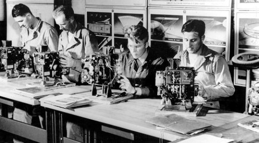 The bombsight was the key to successful missions. Here, Lowry students inspect and adjust Sperry bombsights.