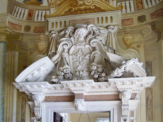 """Villa Capra """"La Rotonda"""" (1560) in Vicenza, Italy by Andrea Palladio. Detail of ornamental """"open pedimant"""" doorway. Detailed fresco paintings fill the wall and ceiling behind the door frame."""