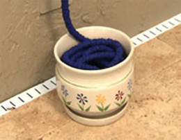 Storage Option for your XHose blue pocket hose coiled inside a small flower pot with painted flowers on the outside