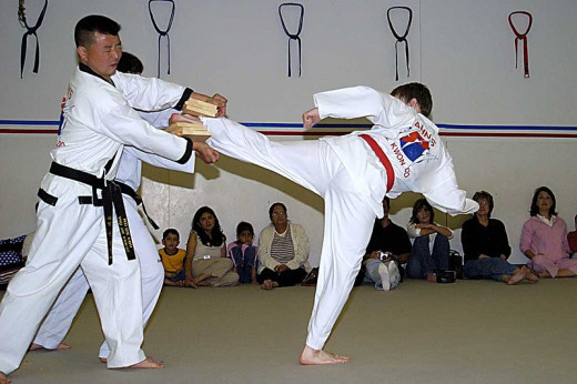 Taekwondo student breaking boards with a side kick.