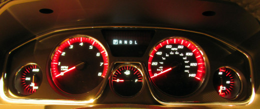 Acadia offers a sporty view through the wheel at GMCs signature red instrument panel, with optional HUD available (not pictured)