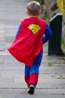 I Am A Superhero, Little boy dressed up like Superman walking boldly down the street.