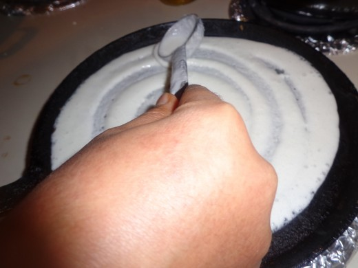 Pour dosa batter on the tawa and spread in a circular motion