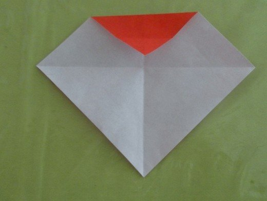 Unfold the paper. There is now a crease line on the top red flap.