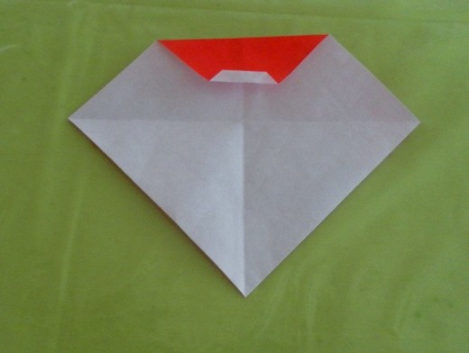Fold upwards the folded edge so that the edge meets the red crease line.