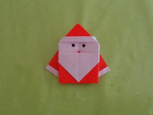 Use a black marker to draw the eyes and a red marker for the mouth. There's your little origami santa. Isn't he cute?