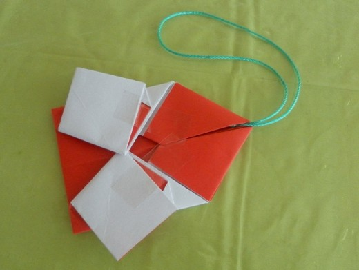 Use sticky tape to hold the paper down. Attach a string to the origami ornament for hanging.
