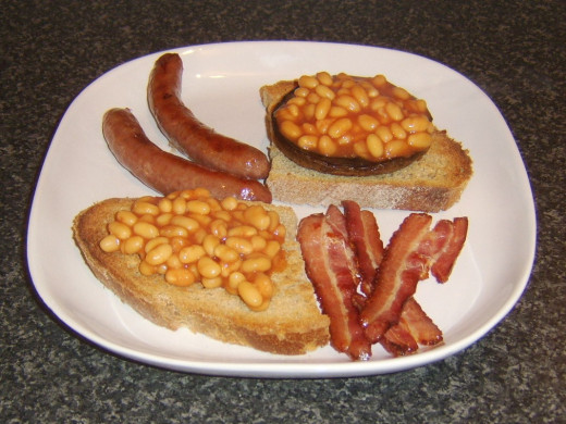 Sausages and bacon are plated with beans on toast