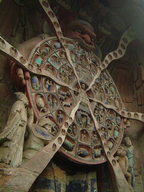Buddhist relief from the Dazu Rock Carvings in China, built sometime between the years 1177 and 1249, Mara, Lord of Death and Desire, clutches the Wheel of Reincarnation, which outlines the Buddhist cycle of reincarnation.