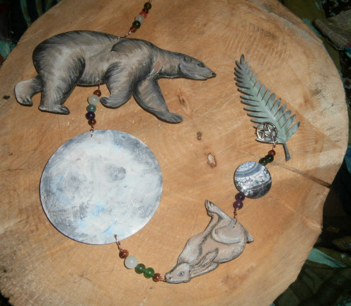 This spirit hanger features a bear, a large moon, a hare, a smaller moon and some bracken fern.