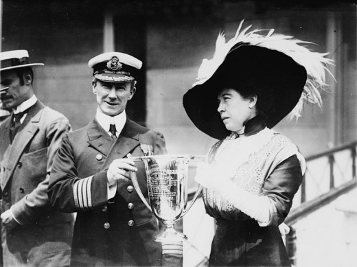 """Mrs. J.J. """"Molly"""" Brown presenting trophy cup award to Capt. Arthur Henry Rostron, for his service in the rescue of the Titanic."""
