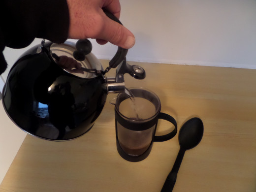 Pour the hot water into the french press and directly into the ground coffee.