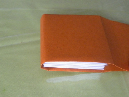Wrap the cover over the pages and fold both ends of the paper inwards to make the front and back covers.