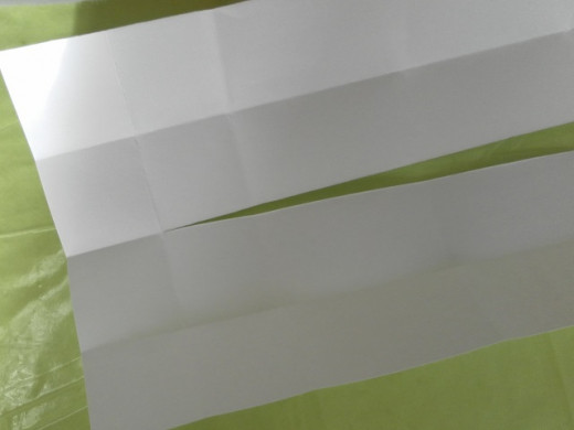 Using a cutter or a pair of scissors, starting from the first vertical crease line on the left, make a cut along the middle horizontal crease line all the way to the other end of the paper.