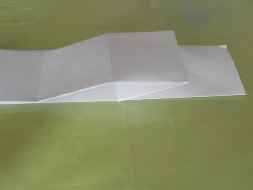 Start folding small squares from the other (right) end of the top flap of the paper, using the vertical crease lines as guides.