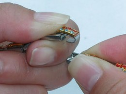how to handle and add Italian charms with open charm detailed with two hands holding the charm in the open position