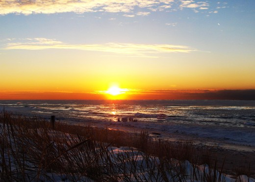 Small ice chunks beginning to form a new ice sheet during a calm Lake Michigan sunset