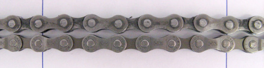 A worn out chain (top) next to a new one (bottom). Note how the worn chain has been stretched over time.
