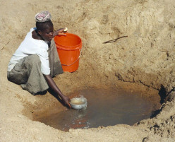 Woman gathering water (most likely contaminated) from a borehole in Tanzania.