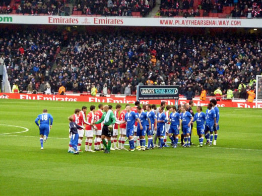 Players of Arsenal F.C. and Everton F.C. shaking hands before a Barclays Premier League match at the Emirates Stadium.