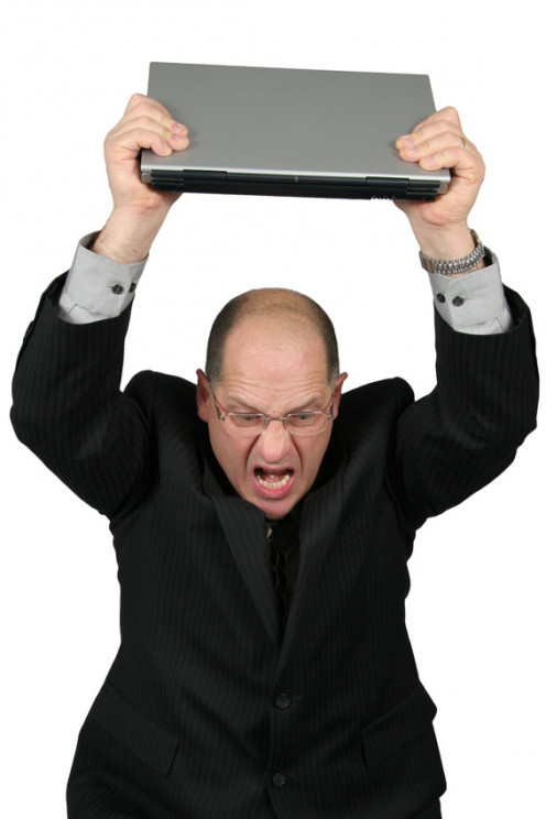 Angry businessman with computer.