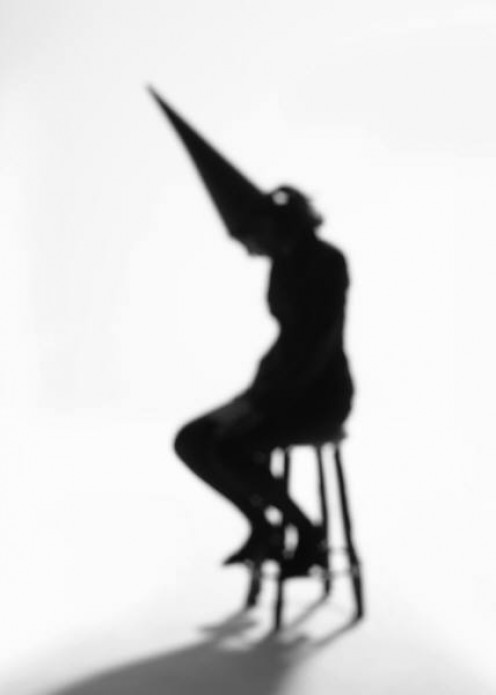 Shadow of a woman wearing a dunce hat.
