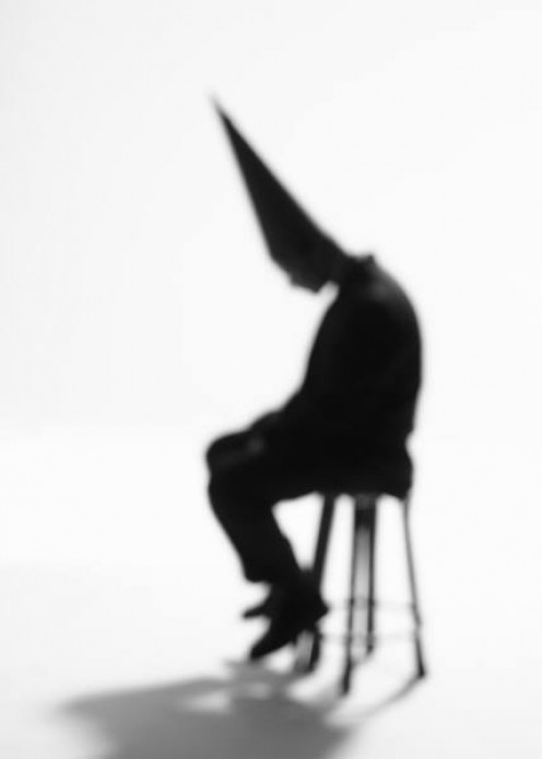 Shadow of a man wearing a dunce hat.