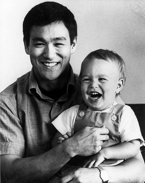 """photo of Bruce Lee with son Brandon. Per source, the photo was accompanied by an original color press kit folder for Enter the Dragon."""" This is standard publicity style promotional photo."""
