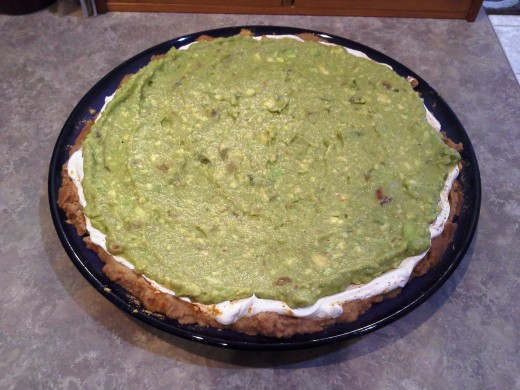 "Step Five: Follow my recipe for ""Quick and Easy Creamy Guacamole Dip"" using three avocados, and spread this mixture on top of your sour cream and taco seasoning, leaving the bottom layers exposed on the edges"