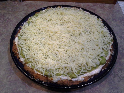 Step Seven: Finish your beautiful 7-Layer Dip with a thick layer of shredded cheese