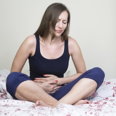 Women holding her stomach in pain.