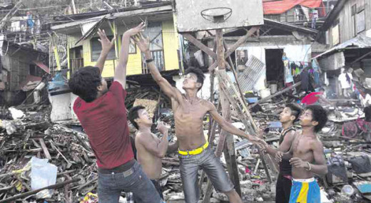Yoland survivors playing basketball in a destroyed neighborhood.