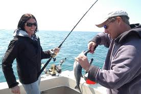 This fisherwoman is well prepared with both a jacket and sunglasses while the charter boat mate helps her with the fish.