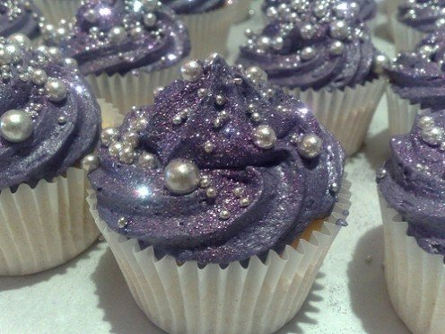 Glitter dust frosting on top of purple frosting with edible beads