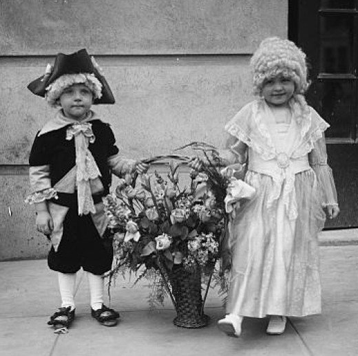 Children dressed in colonial costumes with basket of flowers