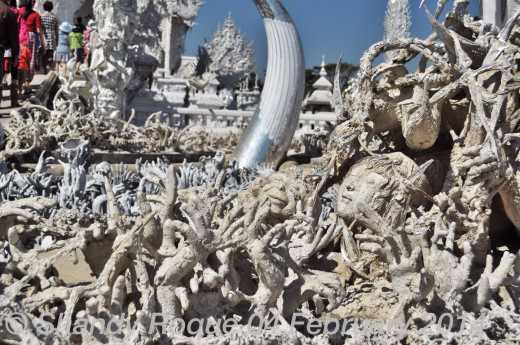 Spirits reaching out in their desperation to escape from hell. And, in the middle of it all is a lovely face and a monkey's head. Could this be the punishment for vanity? Location: Wat Rong Khun (The White Temple)