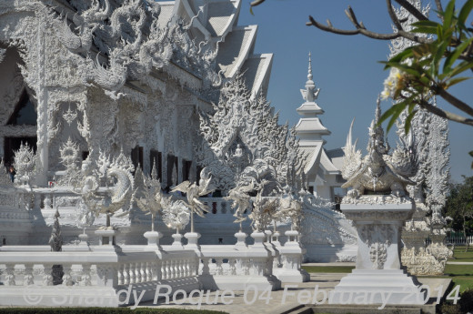 The prayer hall is surrounded by mystical creatures. On each side of the prayer hall are images of the Buddha. Location: Wat Rong Khun (The White Temple)