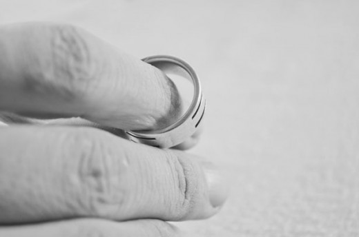 Black and white photo of a man with a wedding band halfway off of his finger.
