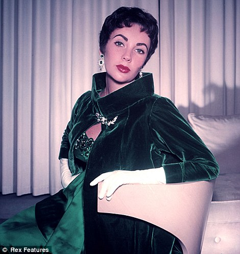 Elizabeth Taylor, showing off rich jewel tones in her dress and coat.