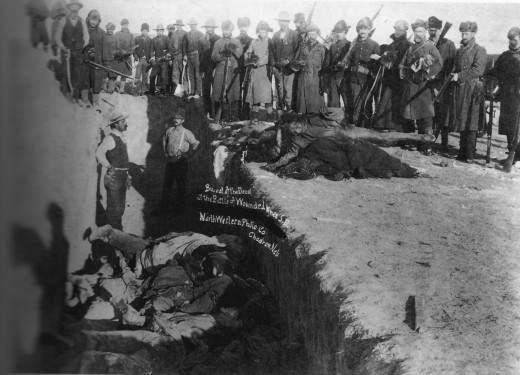 Burial of the dead after the massacre of Wounded Knee. U.S. Soldiers putting Indians in common grave; some corpses are frozen in different positions. South Dakota.