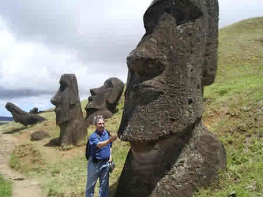 A man standing next to a large moai