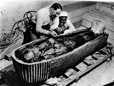 Archaeologist Howard Carter looking over the preserved mummy of Tutankhamun, undisturbed for over three thousand years.