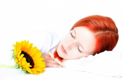Red head womna sleeping next to a sunflower.