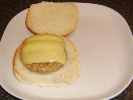 Spicy pork cheeseburger is laid on bread roll