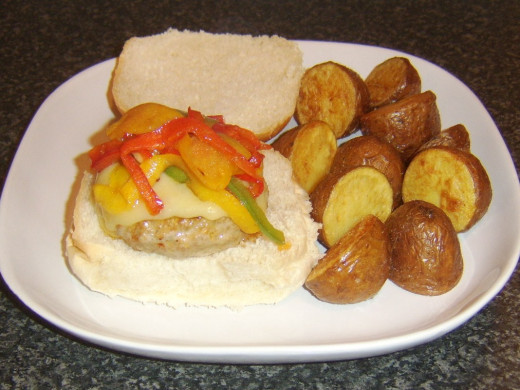 Red potatoes are plated with spicy pork cheeseburger