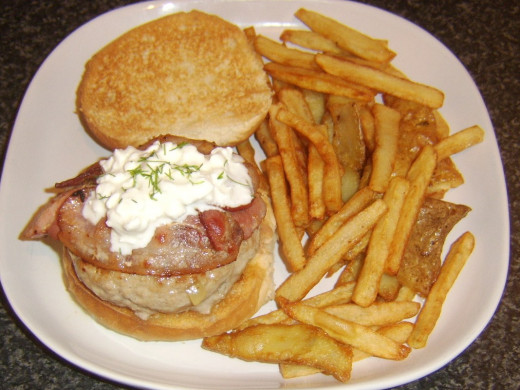 Cottage cheese and chives are laid on pork, sage and onion burger with bacon