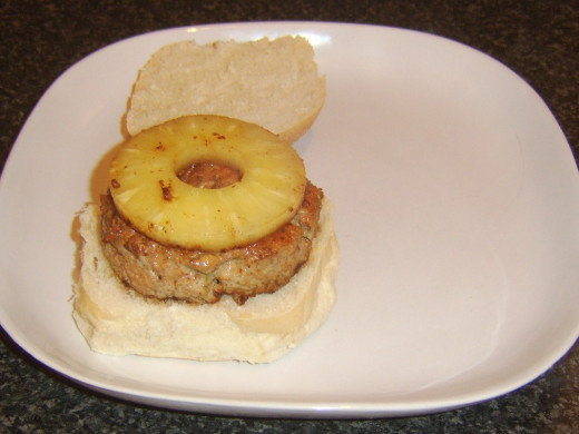 Pineapple ring is laid on sweet and sour pork burger