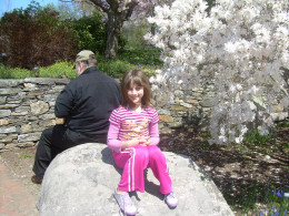 My husband and daughter resting together on a rock by a magnolia tree at Tower Hill Botanical Garden