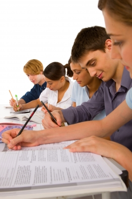 Teenage Students Writing on Book